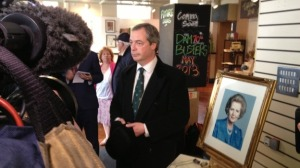 Nigel Farage poses next to a portrait of Margaret Thatcher in 2013